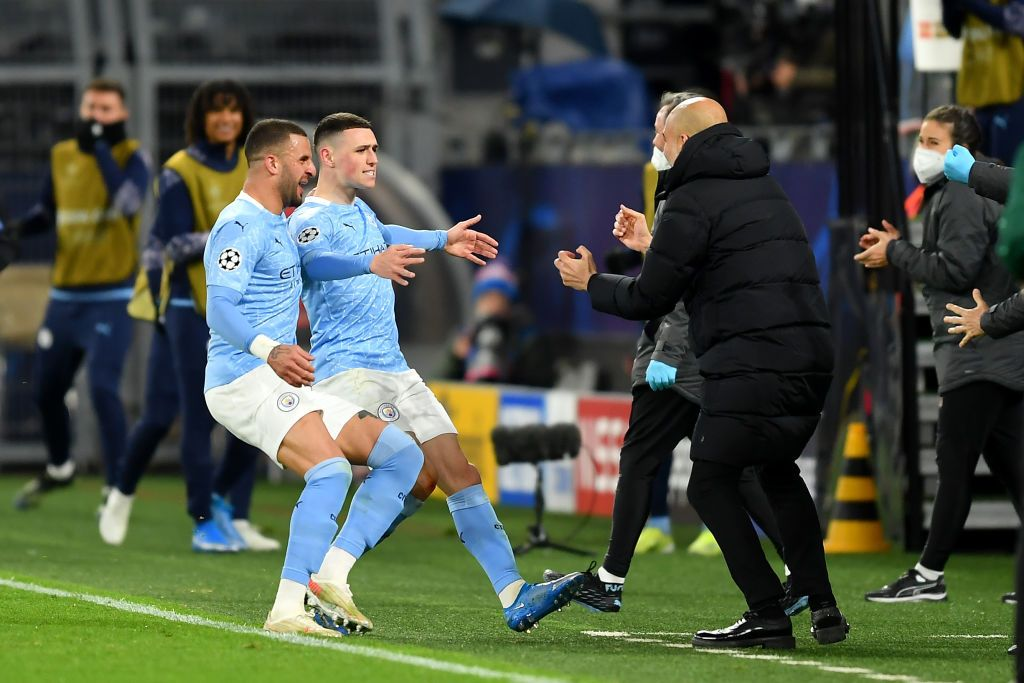 DORTMUND, GERMANY - APRIL 14: Phil Foden of Manchester City runs towards Pep Guardiola, Manager of Manchester City as he celebrates with team mate Kyle Walker after scoring their side's second goal during the UEFA Champions League Quarter Final Second Leg match between Borussia Dortmund and Manchester City at Signal Iduna Park on April 14, 2021 in Dortmund, Germany. Sporting stadiums around Germany remain under strict restrictions due to the Coronavirus Pandemic as Government social distancing laws prohibit fans inside venues resulting in games being played behind closed doors.  (Photo by Friedemann Vogel - Pool/Getty Images)