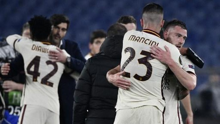 Romas French midfielder Jordan Veretout (R) and Romas Italian defender Gianluca Mancini embrace at the end of the UEFA Europa League quarter final second leg football match AS Rome vs Ajax Amsterdam on April 15, 2021 at the Olympic stadium in Rome. (Photo by Filippo MONTEFORTE / AFP)