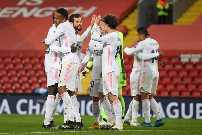 LIVERPOOL, ENGLAND - APRIL 14: Eder Militao of Real Madrid celebrates victory with team mates following the UEFA Champions League Quarter Final Second Leg match between Liverpool FC and Real Madrid at Anfield on April 14, 2021 in Liverpool, England. Sporting stadiums around the UK remain under strict restrictions due to the Coronavirus Pandemic as Government social distancing laws prohibit fans inside venues resulting in games being played behind closed doors. (Photo by Shaun Botterill/Getty Images)
