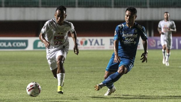 Pesepak bola Persib Bandung Dedi Kusnandar (kanan) berebut bola dengan pesepak bola PS Sleman Irfan Jaya (kiri) saat pertandingan semifinal leg I Piala Menpora 2021 di Stadion Maguwoharjo, Sleman, DI Yogyakarta, Jumat (16/4/2021). ANTARA FOTO/hendra Nurdiyansyah/aww.