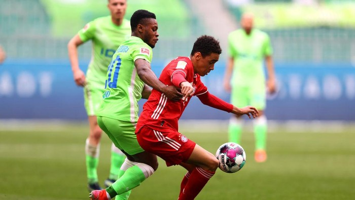 WOLFSBURG, GERMANY - APRIL 17: Jamal Musiala of FC Bayern Muenchen is challenged by Ridle Baku of VfL Wolfsburg during the Bundesliga match between VfL Wolfsburg and FC Bayern Muenchen at Volkswagen Arena on April 17, 2021 in Wolfsburg, Germany. Sporting stadiums around Germany remain under strict restrictions due to the Coronavirus Pandemic as Government social distancing laws prohibit fans inside venues resulting in games being played behind closed doors. (Photo by Martin Rose/Getty Images)