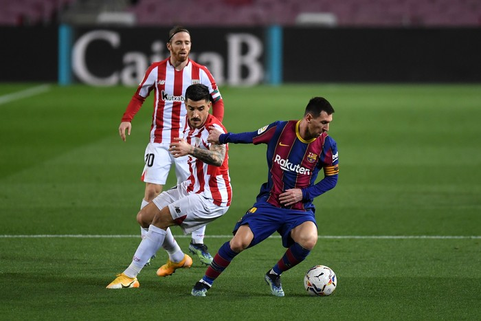 BARCELONA, SPAIN - JANUARY 31: Lionel Messi of Barcelona is challenged by Yuri Berchiche of Athletic Bilbao during the La Liga Santander match between FC Barcelona and Athletic Club at Camp Nou on January 31, 2021 in Barcelona, Spain. Sporting stadiums around Spain remain under strict restrictions due to the Coronavirus Pandemic as Government social distancing laws prohibit fans inside venues resulting in games being played behind closed doors. (Photo by Alex Caparros/Getty Images)