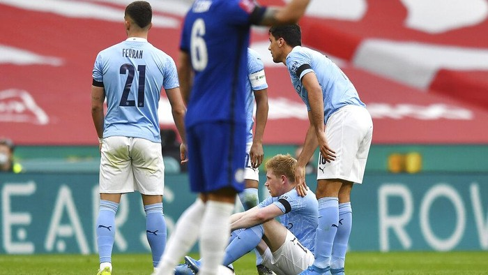 Manchester Citys Kevin De Bruyne sits on the field after injuring during the English FA Cup semifinal soccer match between Chelsea and Manchester City at Wembley Stadium in London, England, Saturday, April 17, 2021. (Ben Stansall, Pool via AP)