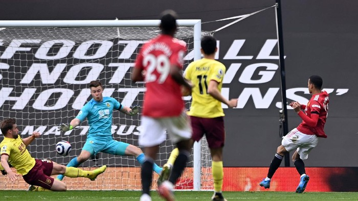 MANCHESTER, ENGLAND - APRIL 18: Mason Greenwood of Manchester United scores his teams first goal past Bailey Peacock-Farrell of Burnley during the Premier League match between Manchester United and Burnley at Old Trafford on April 18, 2021 in Manchester, England. Sporting stadiums around the UK remain under strict restrictions due to the Coronavirus Pandemic as Government social distancing laws prohibit fans inside venues resulting in games being played behind closed doors. (Photo by Stu Forster/Getty Images)