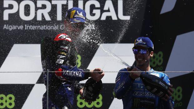 MotoGP - Portuguese Grand Prix - Algarve International Circuit, Portimao, Portugal - April 18, 2021 Monster Energy Yamaha MotoGP's Fabio Quartararo sprays champagne as he celebrates on the podium after winning the race alonside third placed Team Suzuki Ecstar's Joan Mir REUTERS/Pedro Nunes