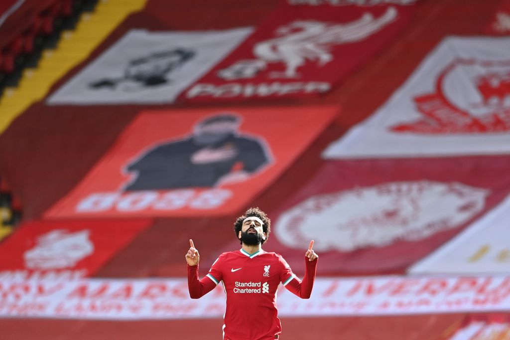 LIVERPOOL, ENGLAND - APRIL 10: Mohamed Salah of Liverpool celebrates after scoring their team's first goal during the Premier League match between Liverpool and Aston Villa at Anfield on April 10, 2021 in Liverpool, England. Sporting stadiums around the UK remain under strict restrictions due to the Coronavirus Pandemic as Government social distancing laws prohibit fans inside venues resulting in games being played behind closed doors.  (Photo by Laurence Griffiths/Getty Images)