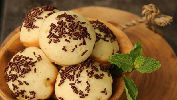 Kue Cubit, a popular street food and snack from Betawi, Jakarta. It is the Indonesian version of Dutch's poffertjes; with added topping of chocolate sprinkles instead of powder sugar. The kue cubit are arranged on a natural wooden bowl. A wooden block is used as the base; which then placed on a metal baking sheet.