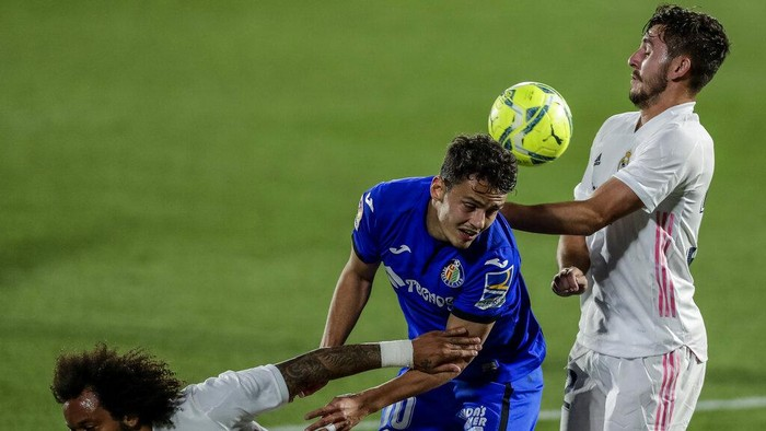 Getafes Enes Unal, center, duels for the ball with Real Madrids Victor Chust, right, and Real Madrids Marcelo during the Spanish La Liga soccer match between Getafe and Real Madrid at the Alfonso Perez stadium in Getafe, Spain, Sunday, April 18, 2021. (AP Photo/Manu Fernandez)