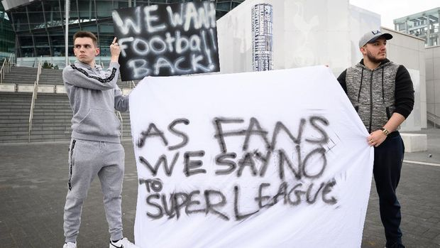 LONDON, UNITED KINGDOM - APRIL 20: Manchester United fan Jack Newson (L) and Tottenham Hotspur fan Cameron Bull hold their handmade signs as they protest against the proposed Super League outside the Tottenham Hotspur stadium on April 20, 2021 in London, United Kingdom. Six English premier league teams have announced they are part of plans for a breakaway European Super League. Arsenal, Manchester United, Manchester City, Liverpool, Chelsea and Tottenham Hotspur will join 12 other European teams in a closed league similar to that of the NFL American Football League. In a statement released last night, the new competition