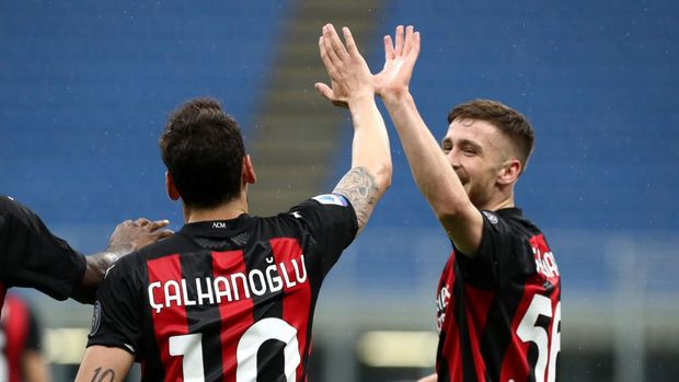 MILAN, ITALY - APRIL 21: Hakan Calhanoglu of A.C. Milan celebrates after scoring their sides first goal with team mate Alexis Saelemaekers during the Serie A match between AC Milan  and US Sassuolo at Stadio Giuseppe Meazza on April 21, 2021 in Milan, Italy.Sporting stadiums around Italy remain under strict restrictions due to the Coronavirus Pandemic as Government social distancing laws prohibit fans inside venues resulting in games being played behind closed doors. (Photo by Marco Luzzani/Getty Images)