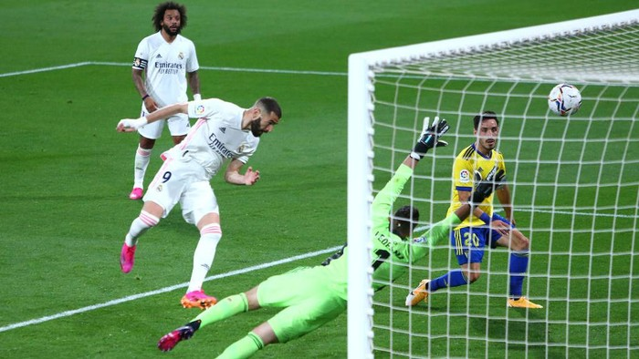 CADIZ, SPAIN - APRIL 21: Karim Benzema of Real Madrid scores their sides third goal past Simone Aresti of Cagliari Calcio during the La Liga Santander match between Cadiz CF and Real Madrid at Estadio Ramon de Carranza on April 21, 2021 in Cadiz, Spain. Sporting stadiums around Spain remain under strict restrictions due to the Coronavirus Pandemic as Government social distancing laws prohibit fans inside venues resulting in games being played behind closed doors. (Photo by Fran Santiago/Getty Images)