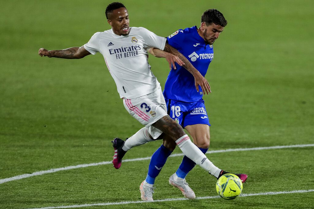 Real Madrid's Eder Militao, left, duels for the ball with Getafe's Mauro Arambarri during the Spanish La Liga soccer match between Getafe and Real Madrid at the Alfonso Perez stadium in Getafe, Spain, Sunday, April 18, 2021. (AP Photo/Manu Fernandez)