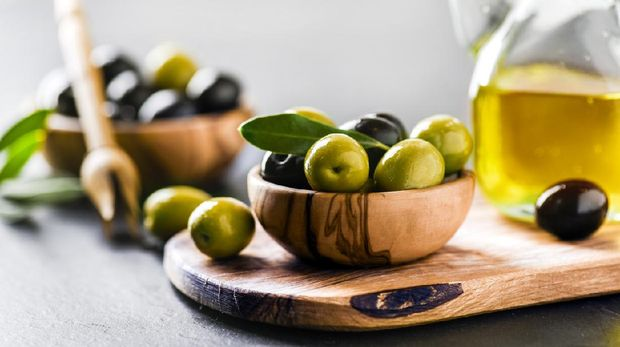 Ripe green and black olives on dark table with vigin oil in old glass bottle. Olive picker and leaves on wooden board.
