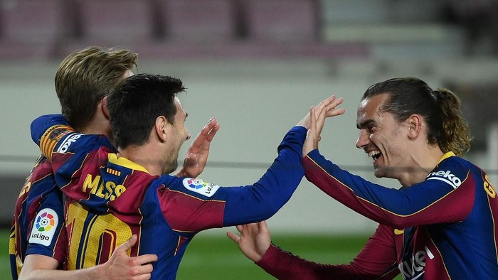 Barcelonas Argentinian forward Lionel Messi celebrates with Barcelonas Dutch midfielder Frenkie De Jong (L) and Barcelonas French midfielder Antoine Griezmann (R) after scoring his teams third goal during the Spanish League football match between Barcelona and Getafe at the Camp Nou stadium in Barcelona on April 22, 2021. (Photo by LLUIS GENE / AFP)