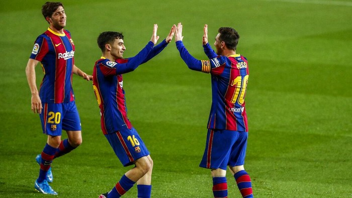 Barcelonas Lionel Messi, right, is congratulated by teammates Pedri, center, Sergi Roberto after scoring the opening goal during the Spanish La Liga soccer match between FC Barcelona and Getafe at the Camp Nou stadium in Barcelona, Spain, Thursday, April 22, 2021. (AP Photo/Joan Monfort)