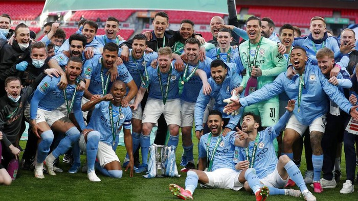 Manchester City players celebrate with the trophy at the end of the English League Cup final soccer match between Manchester City and Tottenham Hotspur at Wembley stadium in London, Sunday, April 25, 2021. Manchester City won 1-0. (AP Photo/Alastair Grant)