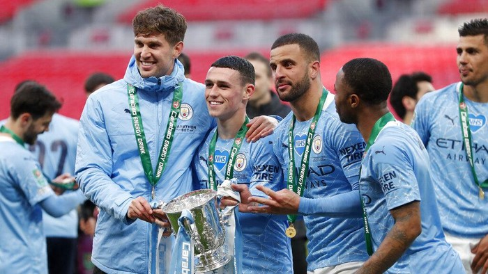 Manchester City players John Stones, Phil Foden, Kyle Walker and Raheem Sterling, from left to right, pose with the trophy at the end of the English League Cup final soccer match between Manchester City and Tottenham Hotspur at Wembley stadium in London, Sunday, April 25, 2021. Manchester City won 1-0. (AP Photo/Alastair Grant)