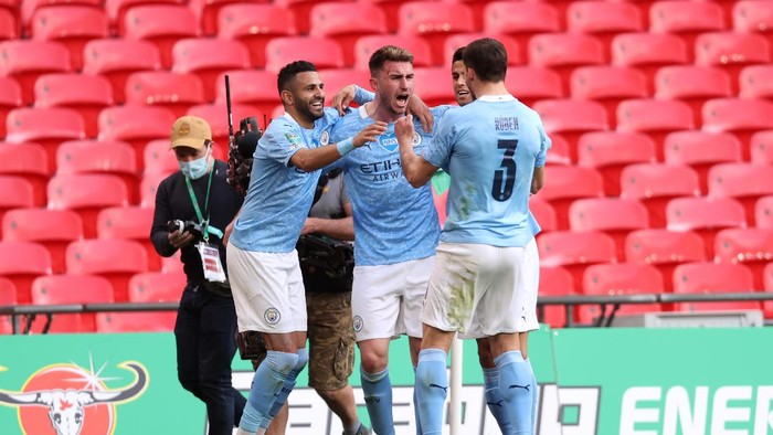 LONDON, ENGLAND - APRIL 25: Aymeric Laporte of Manchester City celebrates with Riyad Mahrez and Ruben Dias after scoring their sides first goal during the Carabao Cup Final between Manchester City and Tottenham Hotspur at Wembley Stadium on April 25, 2021 in London, England. 8,000 fans are due to watch the game at Wembley, the most at an outdoor sporting event in the UK since the coronavirus pandemic started in March, 2020. Each team has been given an allocation of 2,000 with the remaining tickets split between local residents and NHS staff. (Photo by Clive Rose/Getty Images)