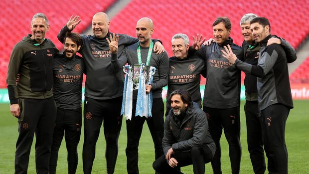 LONDON, ENGLAND - APRIL 25: Pep Guardiola, Manager of Manchester City and his backroom staff celebrates with the trophy after winning the Carabao Cup after the Carabao Cup Final between Manchester City and Tottenham Hotspur at Wembley Stadium on April 25, 2021 in London, England. 8,000 fans are due to watch the game at Wembley, the most at an outdoor sporting event in the UK since the coronavirus pandemic started in March, 2020. Each team has been given an allocation of 2,000 with the remaining tickets split between local residents and NHS staff. (Photo by Clive Rose/Getty Images)