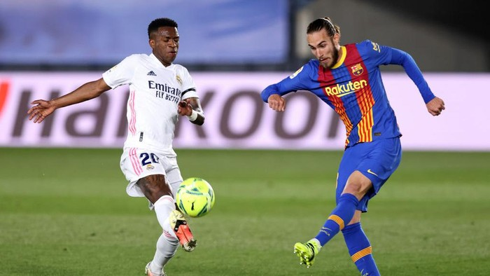 MADRID, SPAIN - APRIL 10: Oscar Mingueza of FC Barcelona is challenged by Vinicius Junior of Real Madrid  during the La Liga Santander match between Real Madrid and FC Barcelona at Estadio Alfredo Di Stefano on April 10, 2021 in Madrid, Spain. Sporting stadiums around Spain remain under strict restrictions due to the Coronavirus Pandemic as Government social distancing laws prohibit fans inside venues resulting in games being played behind closed doors.  (Photo by Angel Martinez/Getty Images)