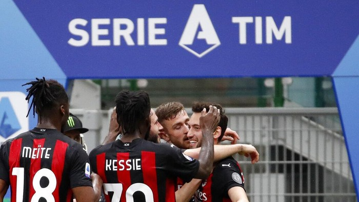AC Milans Hakan Calhanoglu celebrates with teammates after scoring his sides opening goal during the Serie A soccer match between AC Milan and Sassuolo at the San Siro stadium, in Milan, Italy, Wednesday, April 21, 2021. (AP Photo/Antonio Calanni)