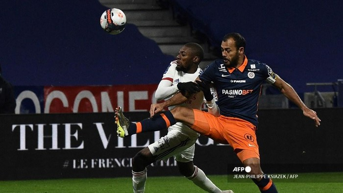 Lyon's Cameroonian forward Toko Ekambi (L) fights for the ball with  Montpellier's Brazilian defender Vitorino Hilton (R)  during the French L1 football match between Lyon (OL) and Montpellier (MHSC) on February 13, 2021, at the Groupama stadium in Dcine-Charpieu near Lyon. (Photo by JEAN-PHILIPPE KSIAZEK / AFP)
