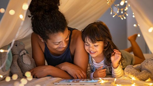 African mother and cute smiling girl using digital tablet while lying in illuminted tent in kid bedroom. Cheerful ethnic woman and lovely daughter on video call under a cozy hut. Lovely little girl with mom watching cartoon on digital tablet in bedroom.
