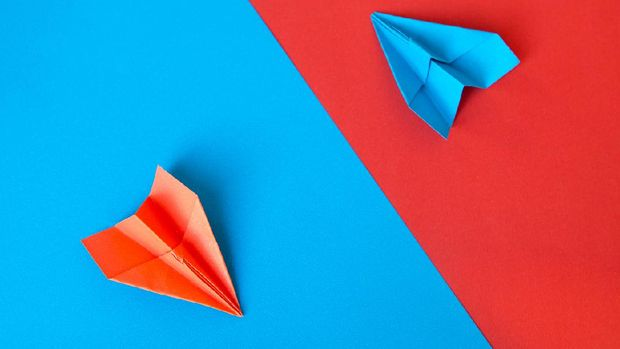 Paper plane on blue and red paper