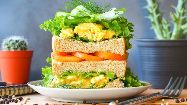 Scrambled eggs sandwich breakfast with fresh tomato sliced, cucumber sliced and green lettuce in front view for healthy breakfast concept.