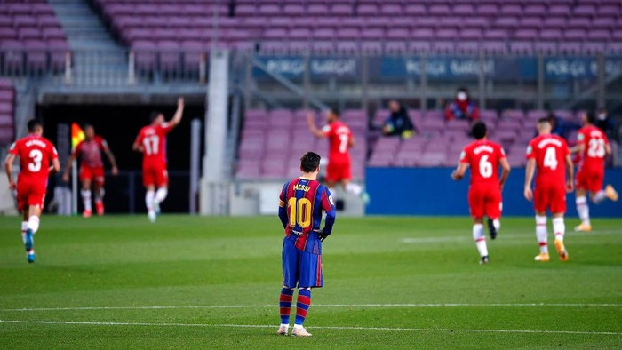BARCELONA, SPAIN - APRIL 29: Lionel Messi of FC Barcelona looks dejected as Darwin Machis of Granada CF celebrates with teammates after scoring their teams first goal during the La Liga Santander match between FC Barcelona and Granada CF at Camp Nou on April 29, 2021 in Barcelona, Spain. Sporting stadiums around Spain remain under strict restrictions due to the Coronavirus Pandemic as Government social distancing laws prohibit fans inside venues resulting in games being played behind closed doors. (Photo by Eric Alonso/Getty Images)