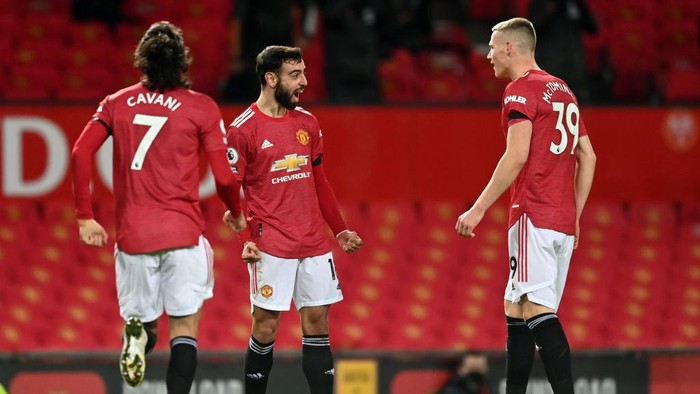 MANCHESTER, ENGLAND - FEBRUARY 06: Bruno Fernandes of Manchester United celebrates with teammates Edinson Cavani and Scott McTominay after scoring their teams second goal during the Premier League match between Manchester United and Everton at Old Trafford on February 06, 2021 in Manchester, England. Sporting stadiums around the UK remain under strict restrictions due to the Coronavirus Pandemic as Government social distancing laws prohibit fans inside venues resulting in games being played behind closed doors. (Photo by Michael Regan/Getty Images)