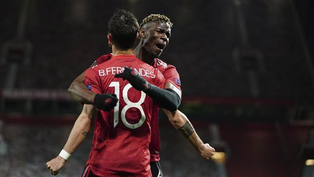 Manchester United's Bruno Fernandes, front, celebrates with Manchester United's Paul Pogba after scoring his side's fourth goal during the Europa League semi final, first leg soccer match between Manchester United and Roma at Old Trafford in Manchester, England, Thursday, April 29, 2021. (AP Photo/Jon Super)