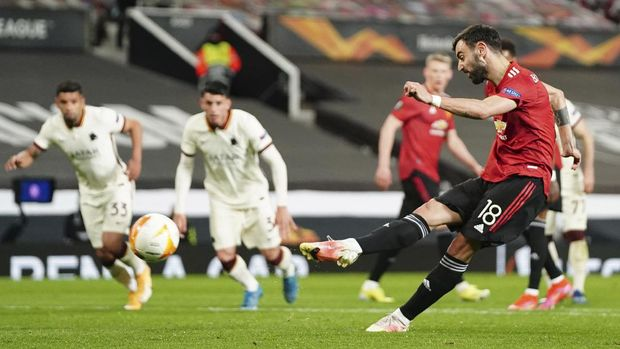 Manchester United's Bruno Fernandes scores his side's fourth goal from penalty during the Europa League semi final, first leg soccer match between Manchester United and Roma at Old Trafford in Manchester, England, Thursday, April 29, 2021. (AP Photo/Jon Super)
