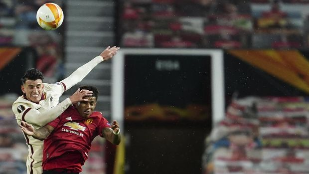 Manchester United's Marcus Rashford, right, jumps for the ball with Roma's Roger Ibanez during the Europa League semi final, first leg soccer match between Manchester United and Roma at Old Trafford in Manchester, England, Thursday, April 29, 2021. (AP Photo/Jon Super)