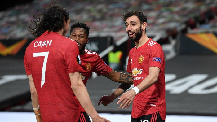 MANCHESTER, ENGLAND - APRIL 29: Bruno Fernandes of Manchester United celebrates with teammates Fred and Edinson Cavani after scoring their teams first goal during the UEFA Europa League Semi-final First Leg match between Manchester United and AS Roma at Old Trafford on April 29, 2021 in Manchester, England. Sporting stadiums around Europe remain under strict restrictions due to the Coronavirus Pandemic as Government social distancing laws prohibit fans inside venues resulting in games being played behind closed doors. (Photo by Michael Regan/Getty Images)