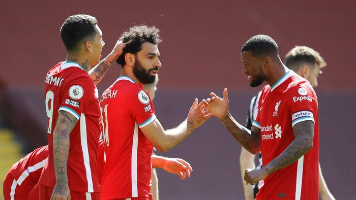 LIVERPOOL, ENGLAND - APRIL 24: Mohamed Salah of Liverpool celebrates with team mates Roberto Firmino and Georginio Wijnaldum after scoring their sides first goal during the Premier League match between Liverpool and Newcastle United at Anfield on April 24, 2021 in Liverpool, England. Sporting stadiums around the UK remain under strict restrictions due to the Coronavirus Pandemic as Government social distancing laws prohibit fans inside venues resulting in games being played behind closed doors.  (Photo by David Klein - Pool/Getty Images)