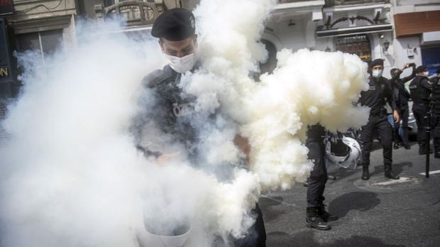 A Turkish policeman stands in a cloud of teargas after he accidentally let off a canister during a May Day rally marking the international day of the worker in Istanbul, on May 1, 2021. - With the highest infection rate in Europe, Turkey enters a full lockdown until May 17, with all non-essential businesses to close and travel between regions restricted. Alcohol sales at groceries and chain stores will be banned to prevent unfair competition with closed small liquor stores. (Photo by BULENT KILIC / AFP)