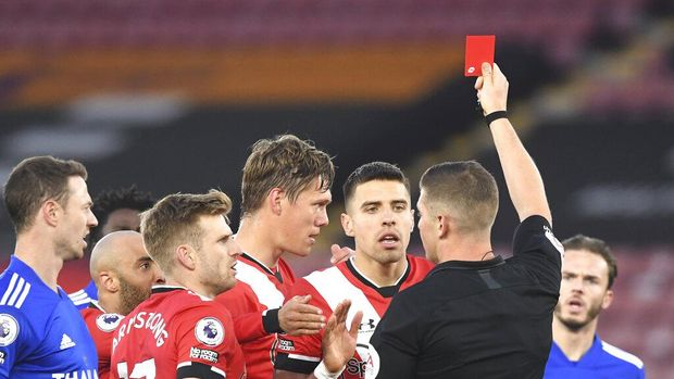 A referee Robert Jones gives red card to Southampton's Jannik Vestergaard, centre, during the English Premier League soccer match between Southampton and Leicester City at St. Mary's Stadium in Southampton, England, Friday, April 30, 2021. (Neil Hall/Pool via AP)