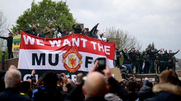 Soccer Football - Manchester United fans protest against their owners before the Manchester United v Liverpool Premier League match - Manchester, Britain - May 2, 2021 Manchester United fans holding a banner in protest against their owners outside the stadium before the match Action Images via REUTERS/Carl Recine