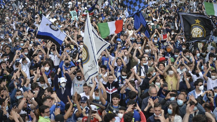 Inter Milan fans celebrate in Piazza Duomo square in front of the gothic cathedral after Inter Milan won its first Serie A title in more than a decade after second-placed Atalanta drew 1-1 at Sassuolo, in Milan, Italy, Sunday, May 2, 2021. Atalanta needed to win to avoid Inter mathematically clinching the title with four matches remaining. It was Inter's first trophy since 2011 and the first Serie A title since 2010. (Claudio Furlan/LaPresse via AP)