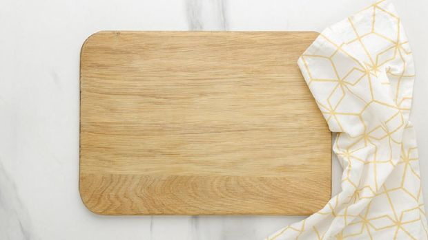 Top view of wooden cutting board, wooden spoons, knife and napkin on the white marble table.Empty space
