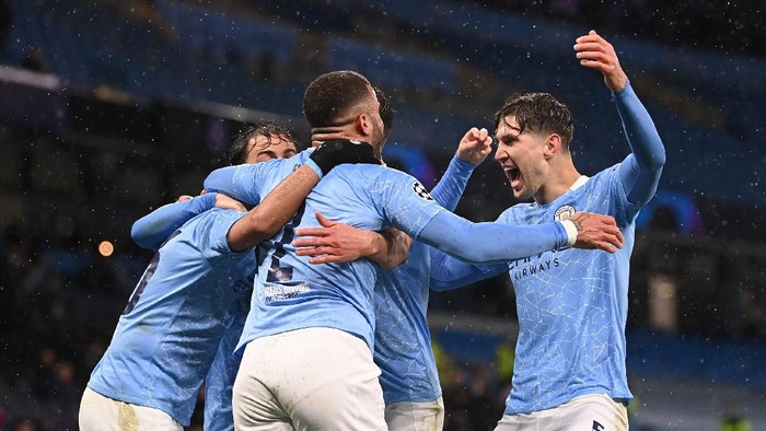 MANCHESTER, ENGLAND - MAY 04: Riyad Mahrez of Manchester City (obscure) celebrates with Kyle Walker and John Stones after scoring his teams second goal during the UEFA Champions League Semi Final Second Leg match between Manchester City and Paris Saint-Germain at Etihad Stadium on May 04, 2021 in Manchester, England. Sporting stadiums around the UK remain under strict restrictions due to the Coronavirus Pandemic as Government social distancing laws prohibit fans inside venues resulting in games being played behind closed doors. (Photo by Laurence Griffiths/Getty Images)