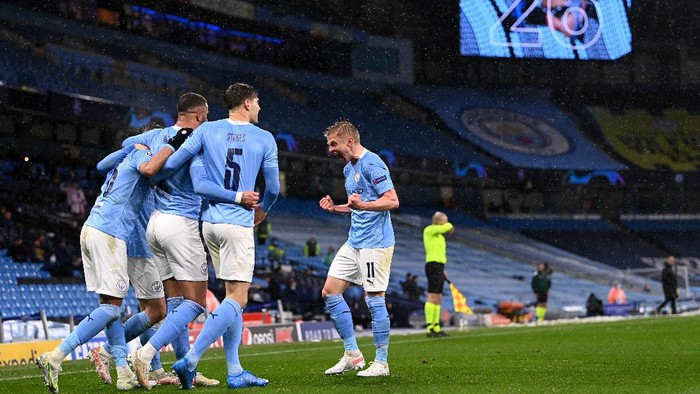 MANCHESTER, ENGLAND - MAY 04: Riyad Mahrez of Manchester City celebrates with Kyle Walker, John Stones and Oleksandr Zinchenko after scoring his teams second goal during the UEFA Champions League Semi Final Second Leg match between Manchester City and Paris Saint-Germain at Etihad Stadium on May 04, 2021 in Manchester, England. Sporting stadiums around the UK remain under strict restrictions due to the Coronavirus Pandemic as Government social distancing laws prohibit fans inside venues resulting in games being played behind closed doors. (Photo by Laurence Griffiths/Getty Images)