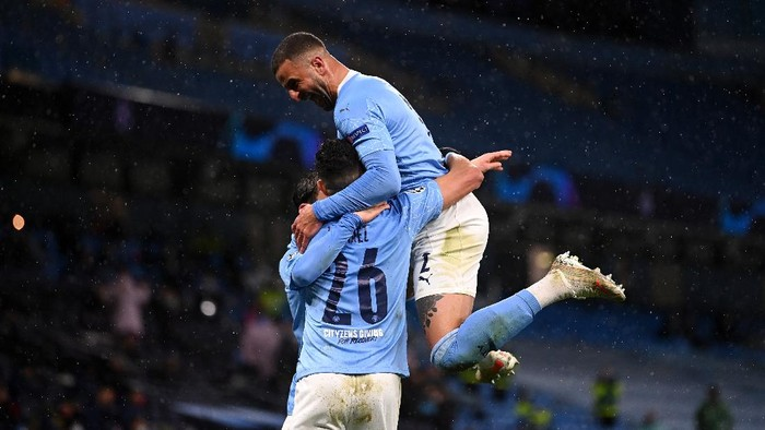 MANCHESTER, ENGLAND - MAY 04: Riyad Mahrez of Manchester City celebrates with Kyle Walker after scoring his teams second goal during the UEFA Champions League Semi Final Second Leg match between Manchester City and Paris Saint-Germain at Etihad Stadium on May 04, 2021 in Manchester, England. Sporting stadiums around the UK remain under strict restrictions due to the Coronavirus Pandemic as Government social distancing laws prohibit fans inside venues resulting in games being played behind closed doors. (Photo by Laurence Griffiths/Getty Images)