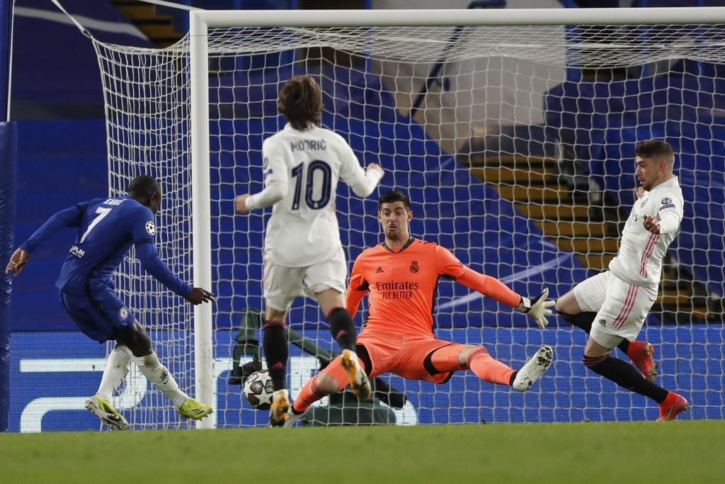 Real Madrid's goalkeeper Thibaut Courtois saves on a kick by Chelsea's N'Golo Kante during the Champions League semifinal 2nd leg soccer match between Chelsea and Real Madrid at Stamford Bridge in London, Wednesday, May 5, 2021. (AP Photo/Alastair Grant)