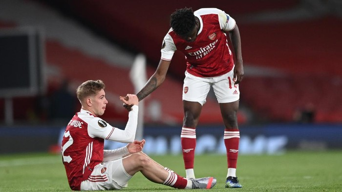 LONDON, ENGLAND - MAY 06: Emile Smith Rowe (L) of Arsenal is helped up by team mate Thomas Partey as they both look dejected following the UEFA Europa League Semi-final Second Leg match between Arsenal and Villareal CF at Emirates Stadium on May 06, 2021 in London, England. Sporting stadiums around Europe remain under strict restrictions due to the Coronavirus Pandemic as Government social distancing laws prohibit fans inside venues resulting in games being played behind closed doors. (Photo by Shaun Botterill/Getty Images)