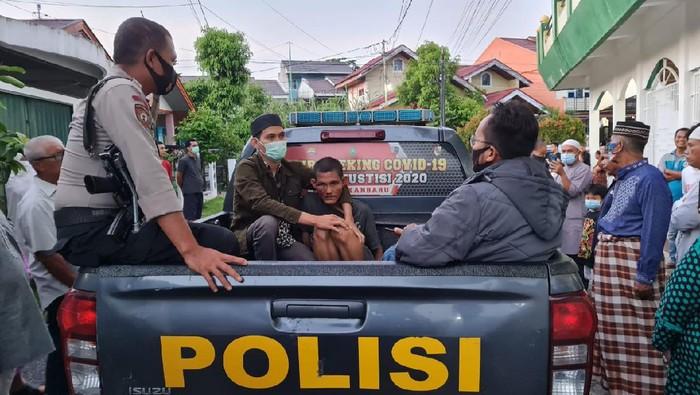 Polisi mengamankan pria pelaku pemukulan terhadap imam masjid di Pekanbaru (dok Istimewa)