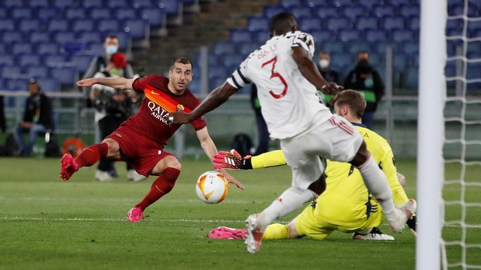 Romas Henrikh Mkhitaryan, left, attempts a shot at goal and misses in front of Manchester Uniteds goalkeeper David de Gea, center, and Manchester Uniteds Eric Bailly during the Europa League semifinal, second leg soccer match between Roma and Manchester United at Romes Olympic stadium, Italy, Thursday, May 6, 2021. (AP Photo/Alessandra Tarantino)