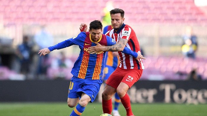 BARCELONA, SPAIN - MAY 08: Lionel Messi of FC Barcelona and Sauel Niguez of Atletico Madrid  battle for the ball  during the La Liga Santander match between FC Barcelona and Atletico de Madrid at Camp Nou on May 08, 2021 in Barcelona, Spain. Sporting stadiums around Spain remain under strict restrictions due to the Coronavirus Pandemic as Government social distancing laws prohibit fans inside venues resulting in games being played behind closed doors. (Photo by David Ramos/Getty Images)