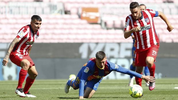 Barcelona's Clement Lenglet, center, fights for the ball with Atletico Madrid's Koke, right, and Atletico Madrid's Angel Correa during the Spanish La Liga soccer match between FC Barcelona and Atletico Madrid at the Camp Nou stadium in Barcelona, Spain, Saturday, May 8, 2021. (AP Photo/Joan Monfort)